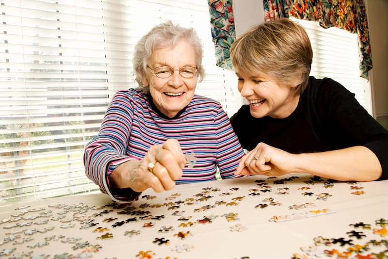 Elderly woman and younger person putting a puzzle together