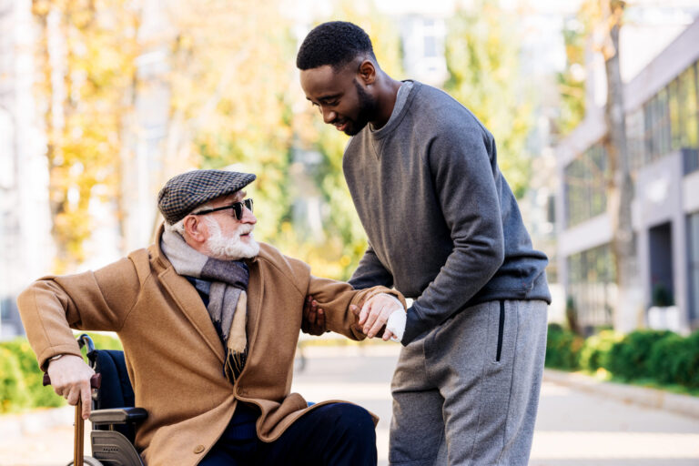 Caregiver helping elderly man out of wheelchair