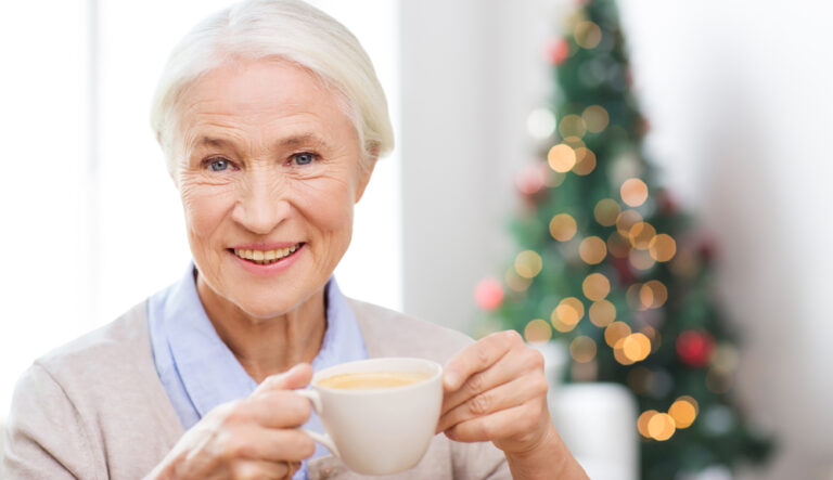 happy senior woman with cup of coffee at home