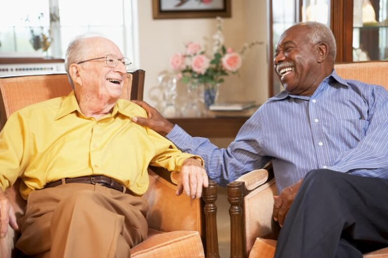 Two elder men visiting with each other sitting in chairs