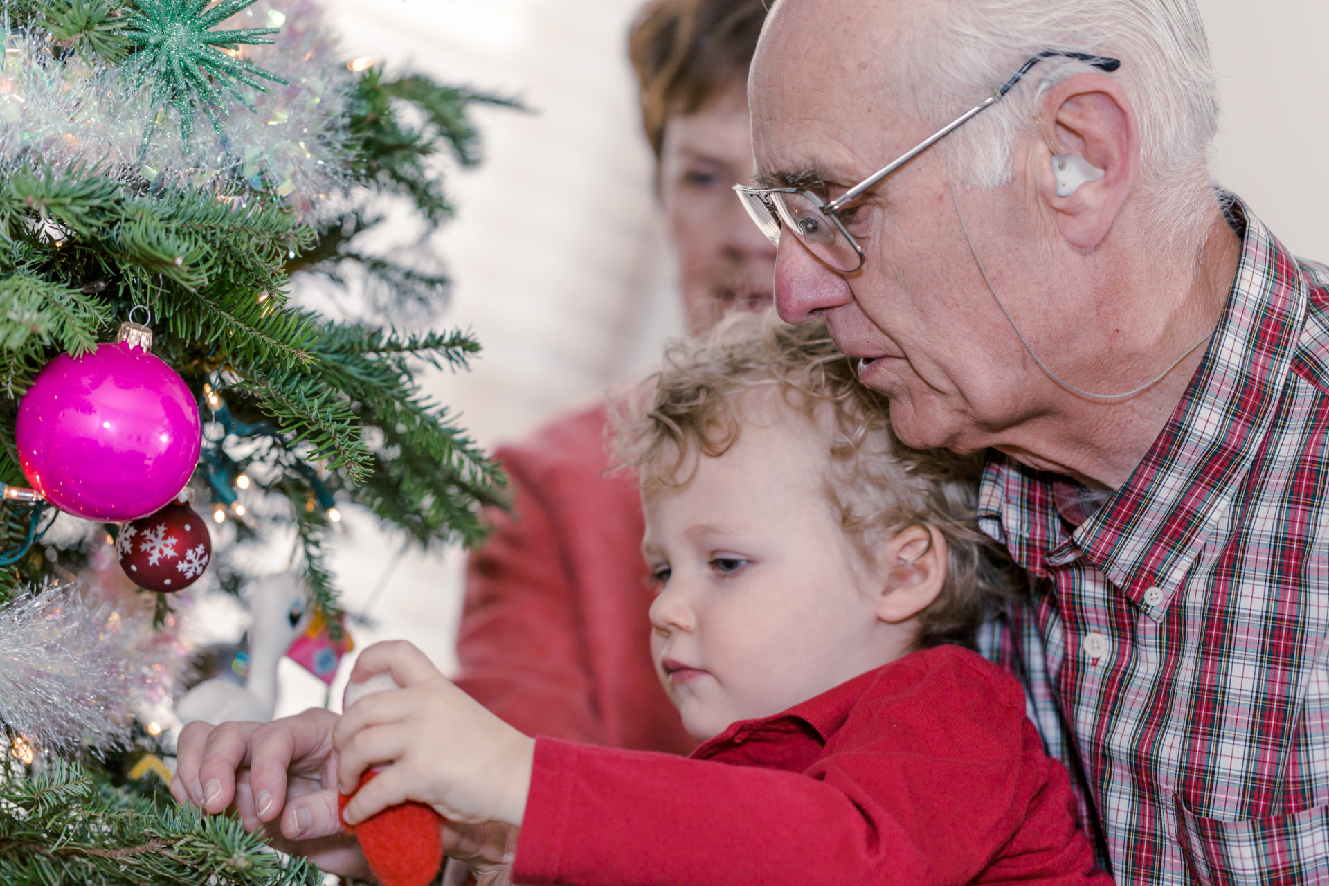 Grandfather lifting grandson to decorate Christmas tree