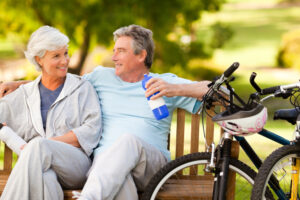 Elderly couple sitting on a bench with their bikes