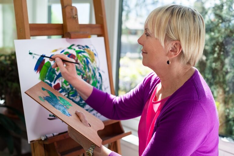 Happy retired woman painting on canvas for fun at home