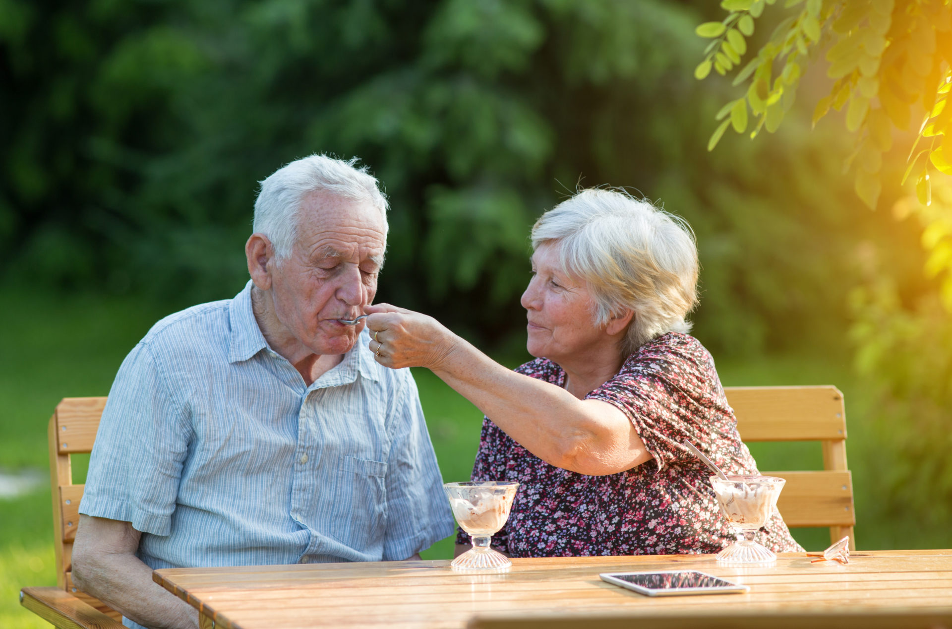 Old couple eating ice cream outside